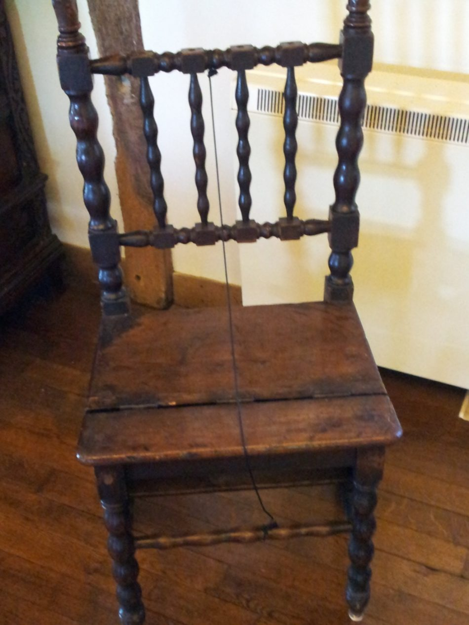 A chair with a turned balusters between the frame.
