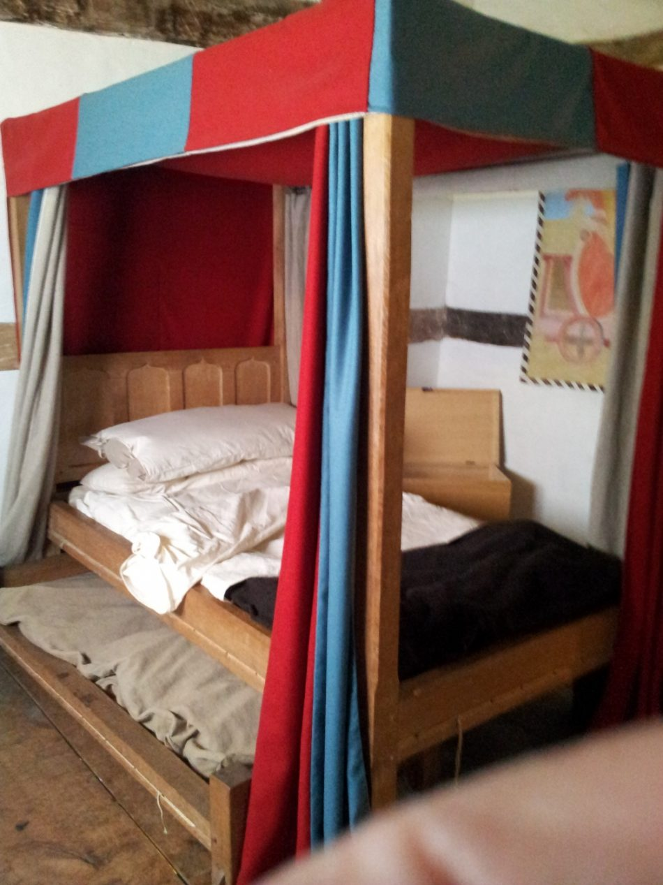A valence and canopy bed with a truckle bed in a poor household.The small truckle bed was usually for children or servants.