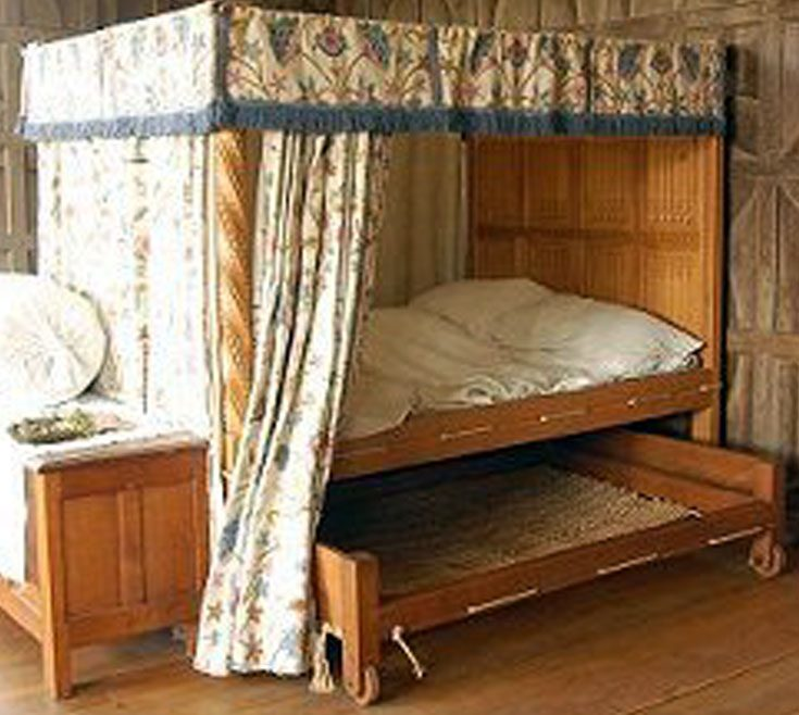 A posted corded bed with a truckle in a wealthy household.It has 5 curtains and a valence. Bed cords trussed between holes in the bed frame to support the mattresses.The cords could be tightened to give better support which led to the saying